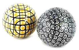 Two similar 19thC Staffordshire type pottery carpet bowls, one with a geometric design in black, the