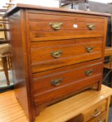 An Edwardian oak chest of three long drawers, with plate back handles.