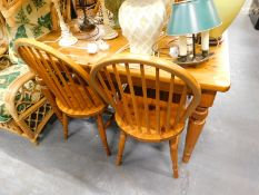 A pine kitchen table with rectangular top, raised on tapering cylindrical legs, 70cm high, and