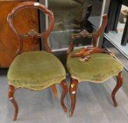 A pair of Victorian mahogany balloon back chairs, each with a green upholstered padded seat on