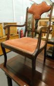 An Edwardian mahogany open armchair, with a padded back and seat.