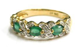 A modern emerald and diamond set 9ct gold dress ring, the design of three opal emeralds cross set wi