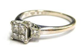 An 18ct white gold diamond set dress ring, with arrangement of four princess cut diamonds on raised