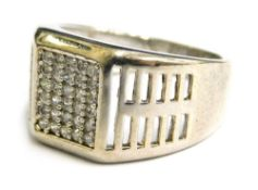 A silver dress ring, with pave set central white stone design and pierced design shoulders, ring siz