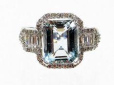 An aquamarine and diamond dress ring, with rectangular cut aquamarine, in four claw white gold setti
