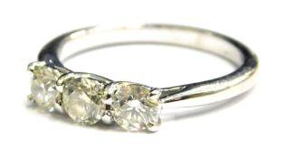 A platinum diamond three stone set dress ring, with three round brilliant cut diamonds, each similar