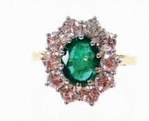 An 18ct gold emerald and diamond cluster ring, with oval cut emerald 8.6mm x 6.6mm x 3.8mm, totallin