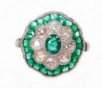 An emerald and diamond daisy style ring, the centre with oval cut emerald, surrounded by old cut dia