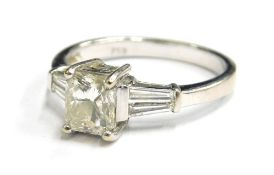 An 18ct white gold diamond dress ring, with central rectangular cut diamond measuring 5.6mm x 4.8mm