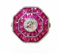 An octagonal ruby and diamond ring, with central round brilliant cut diamond, in rub over setting, 5