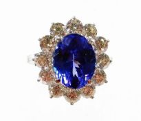 A tanzanite and diamond cluster ring, with oval cut AAA tanzanite, 4.95cts, in four claw setting, su