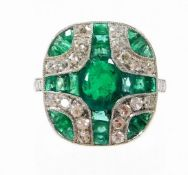 An Art Deco style emerald and diamond ring, with central oval cut emerald and further baguette cut e