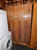 A Heathland Furniture limed oak double wardrobe, with carved panel doors, 188cm high, 126cm wide,
