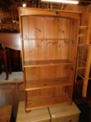 A pine bookcase enclosing three adjustable shelves, 134cm high, 75cm wide, 27cm deep.