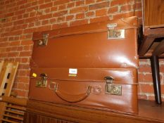 Two brown leatherette suitcases, largest 23cm high, 60cm wide, 23cm deep.