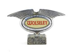 A Wolseley mid 20thC chrome light up grill badge, raised on a marble base, 16cm wide.