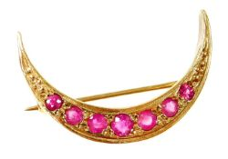 A 9ct gold garnet set crescent brooch, the crescent moon set with seven graduated stones, on a