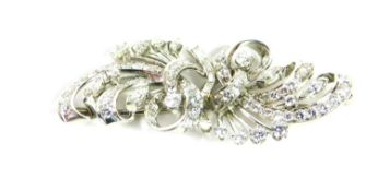 A diamond set spray brooch, of tied scrolling form, set with brilliant and baguette cut diamonds, in