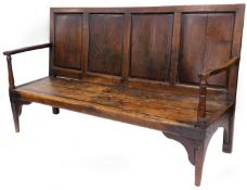 An 18thC elm, oak and pine settle, the back formed possibly with a coffer top, with scroll carved