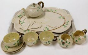 An early 20thC Belleek part tea service, decorated with clover, comprising teapot with bark handle
