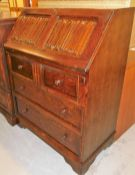 An Old Charm oak bureau, the fall section with red leather tooling, three drawers and filling