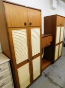 A teak 1970's style bedroom suite, comprising two two door wardrobes, and a wall mountable
