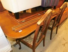 A yew veneered extending twin pedestal dining table and a matched set of four chairs, the table with