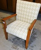 A child's side chair, with beech arms and upholstered in cream patterned fabric. the upholstery in