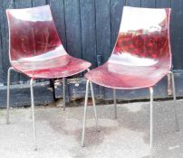 A pair of fibreglass style shaped chairs, with red textured one piece backs and seats, on a chrome