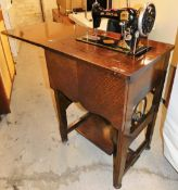 A Jones sewing machine in oak stand, enclosed in a mahogany tailors work stand, with compartment