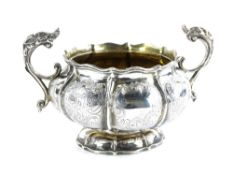 A George III silver two handled sugar bowl, of lobed form, engraved with scrolls etc., the handles