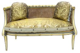 A Regency bergere sofa, painted in cream and powder blue, the frame carved with acanthus, fans and