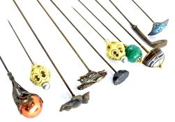 A collection of hat pins, to include a golf club, an Art Nouveau style piece inset with a red