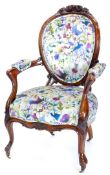 A Victorian walnut showframe armchair, carved with flowers leaves etc., upholstered in vivid