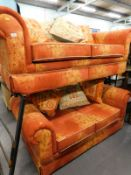 A pair of two seater sofas, in orange and red colour way.