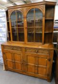 An Old Charm style oak display cabinet, with glazed doors, raised above two frieze drawers, and