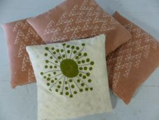 Four modern scatter cushions, three in dusky pink, one in cream/green