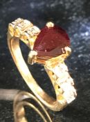 9ct Gold Dress ring with central red faceted stone and CZ stones set to shoulders