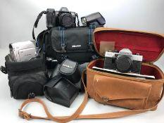 Three vintage cameras to include a Pentax Praktica MTL3, a Minolta Dynax 7000i and a Canon MV890