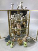 Collection of ceramic animals in a three tier metal display case (height 75cm)