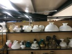 Extensive collection of copper and brass oil lamps, glass shades and chimneys (over two shelves)