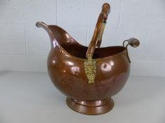 Large copper coal bucket with brass lion head detailing and two wooden handles.