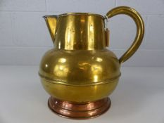 Large brass jug on single copper foot approx. 30cm tall