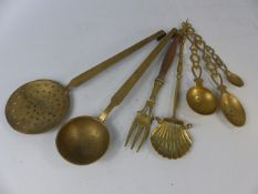 Collection of brass cooking utensils to include three welsh love spoons