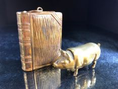 Two brass vesta cases, one in the form of a pig, the other a book