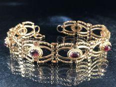 9ct Gold bracelet set with seven garnet oval stones (approx 9.5g)