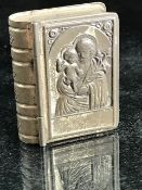 Miniature metal bible-shaped box containing a set of rosary beads