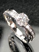 18ct white gold ring with central brilliant cut stone and cross over diamond shoulders