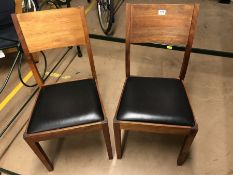 Pair of teak framed dining chairs with Black padded seats