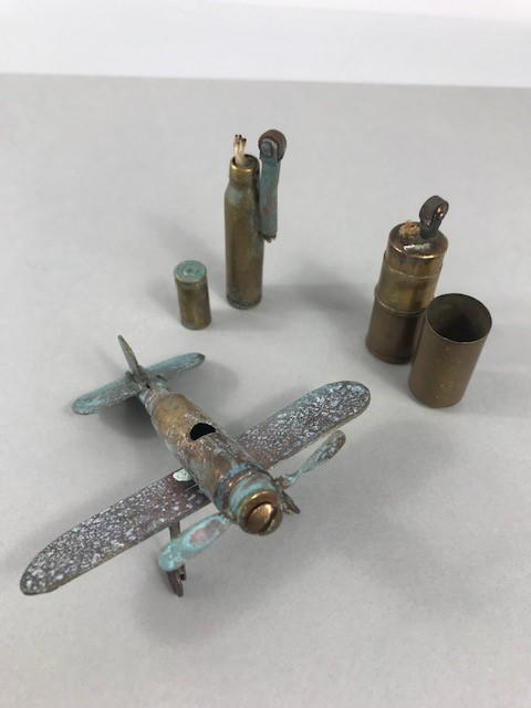 Lot 14 - Two WWI trench art lighters and a trench art model plane